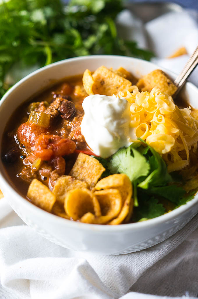 vegetarian chili in a bowl on a white background with sour cream, cheese, and Fritos