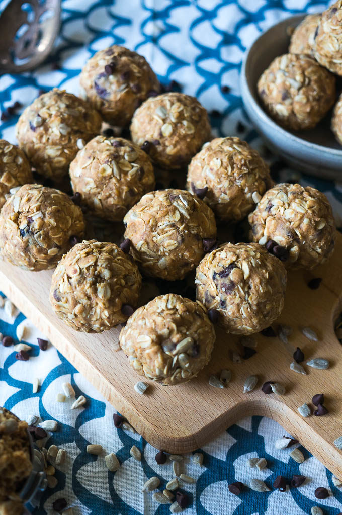 energy balls with sunflower seeds on a wooden cutting board on a white and blue background
