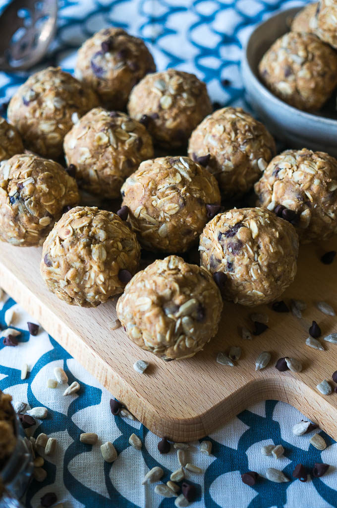energy balls with sunflower seeds on a wooden cutting board with a white and blue background