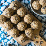 energy balls on a wooden cutting board on a white and blue background