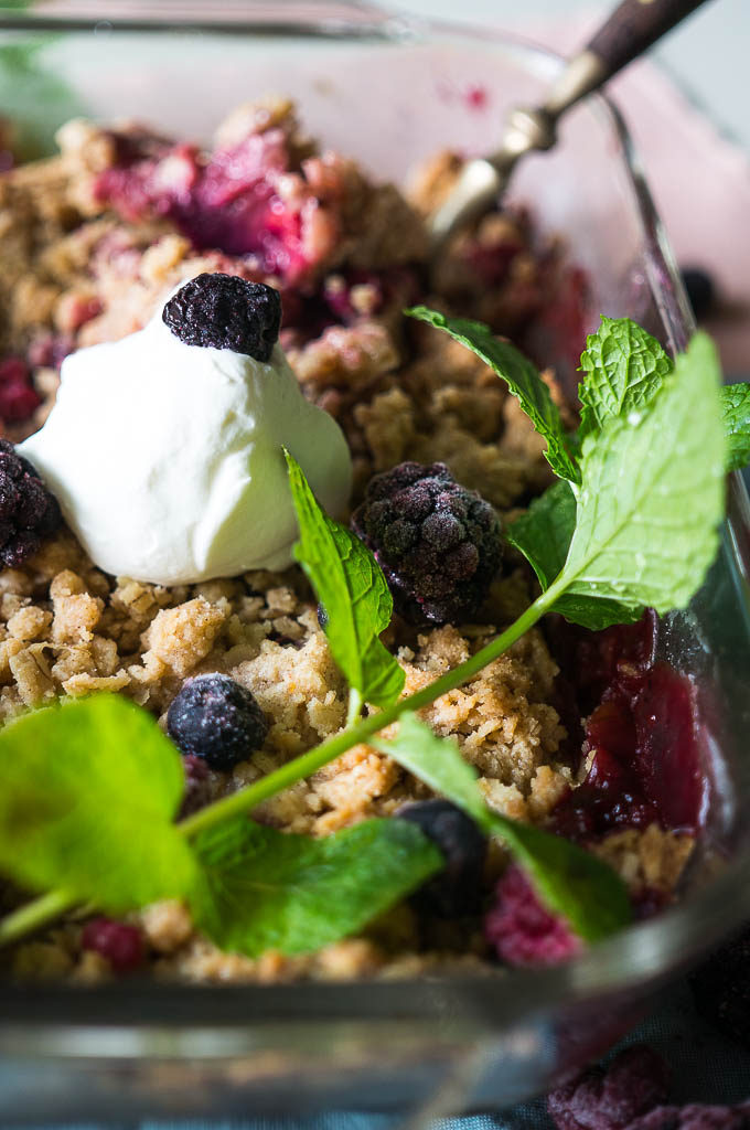 Berry Rhubarb Crisp with whipped topping, mint sprig, on a blue and pink napkin.