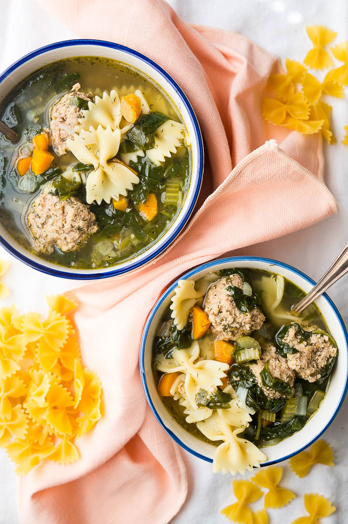 Italian Wedding Soup with turkey meatballs, fresh dill, and bowtie pasta with a silver spoon on a peach napkin and a white tablecloth. Dried bowtie pasta.
