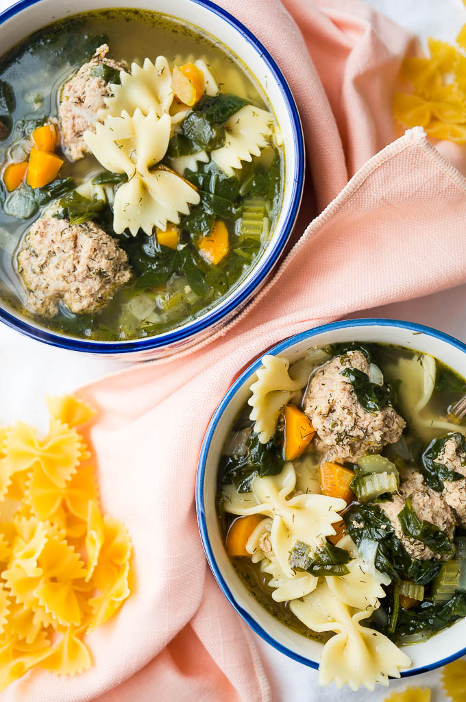 Italian Wedding Soup with turkey meatballs, fresh dill, and bowtie pasta  in a blue and white bowl on a peach napkin and a white tablecloth. Dried bowtie pasta.
