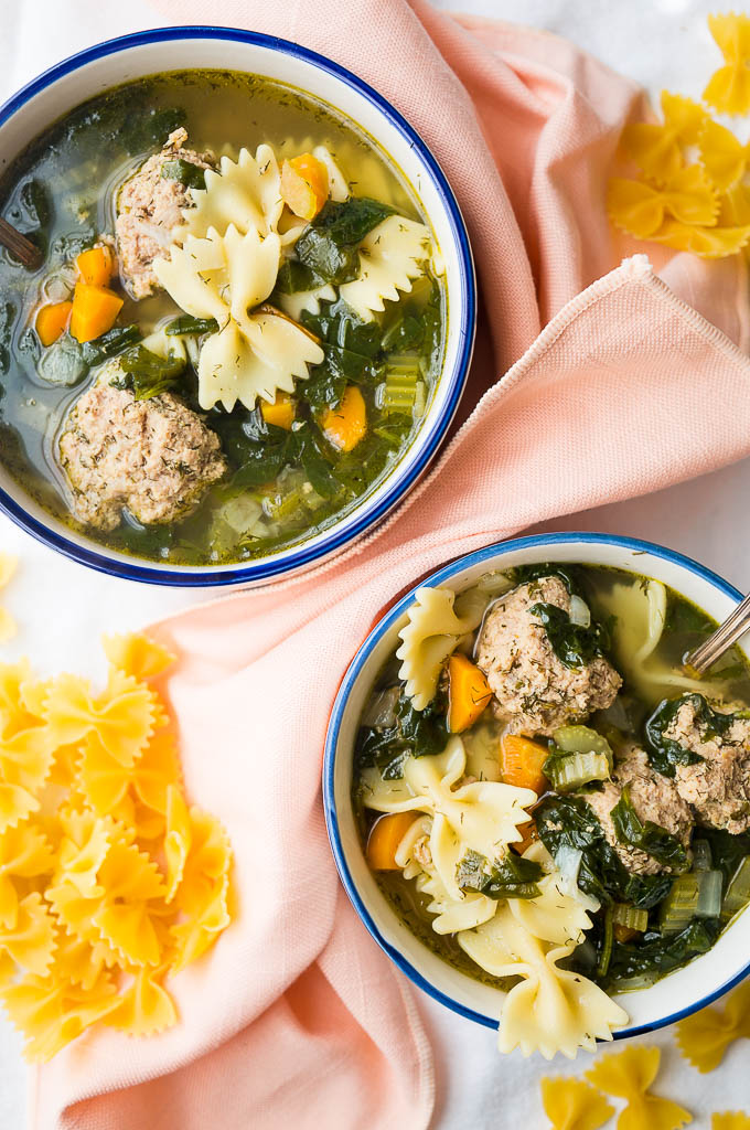 Italian Wedding Soup with turkey meatballs, fresh dill, and bowtie pasta  in a blue and white bowl with a silver spoon on a peach napkin and a white tablecloth. Dried bowtie pasta.