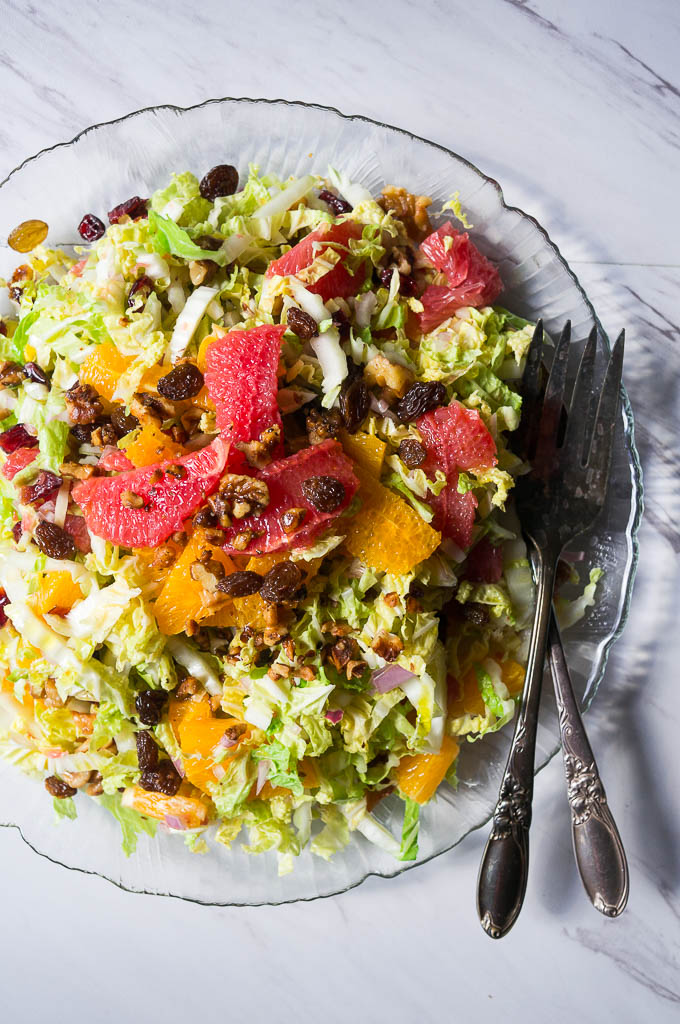 Citrus Salad with Dried Cranberries and Toasted Walnuts. A savory salad showcasing winter citrus fruit, crispy cabbage, and salted toasty walnuts.
