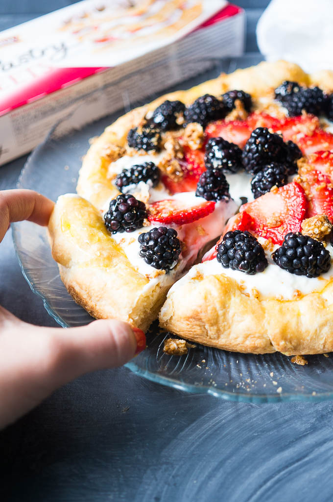 Fruity Granola Breakfast Pizza. Only 5 ingredients! Flaky puff pastry layered with luscious greek yogurt, berries, granola, and drizzled with honey.