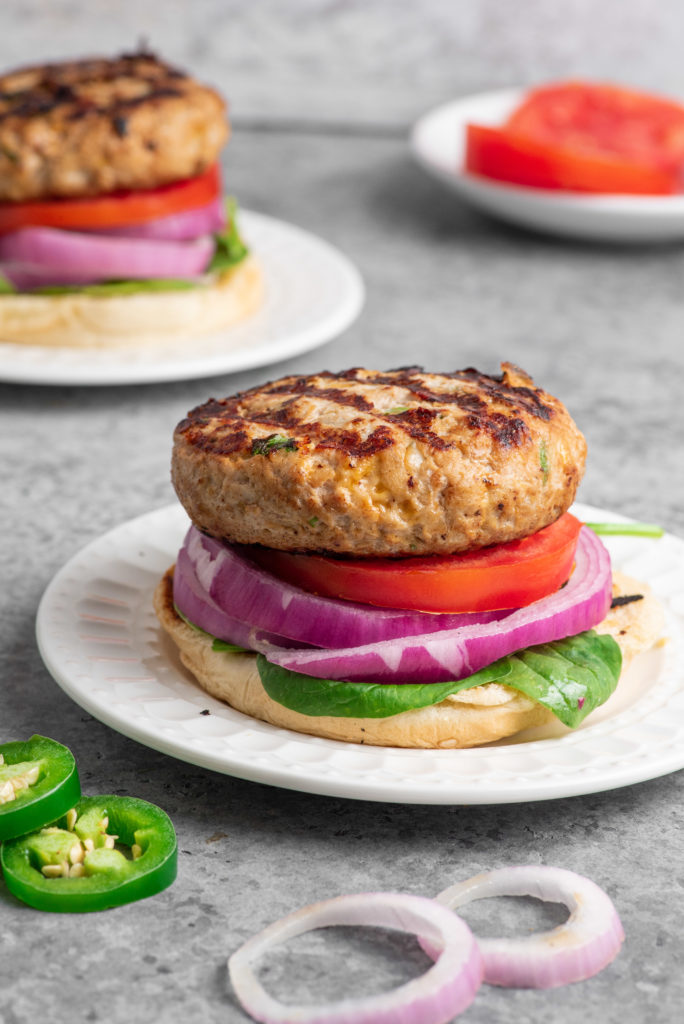 Turkey burgers with toppings on a white background.