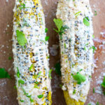 Grilled Mexican Street Corn is lathered in a spicy mayo and sour cream mixture, then sprinkled with cilantro and parmesan cheese.