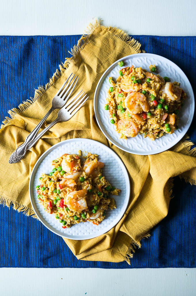 Shrimp paella on white plates with yellow and blue napkins