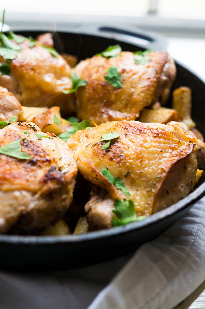 Crispy Lemon Thyme Chicken Thighs over red potatoes and thin sliced onions. The easiest marinade ever and makes the most delicious skin!!