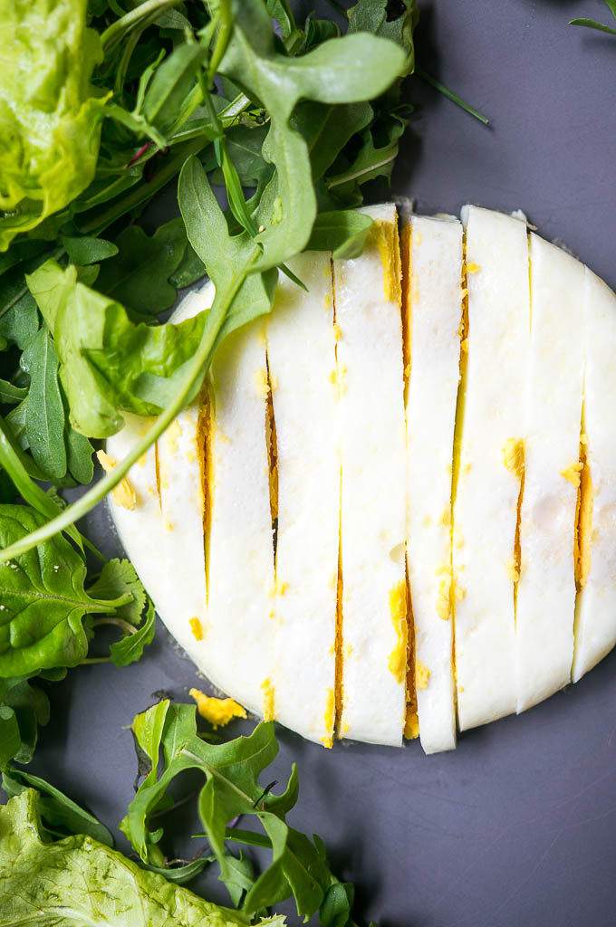 Cooked egg sliced with a side of arugula on a blue grey background.