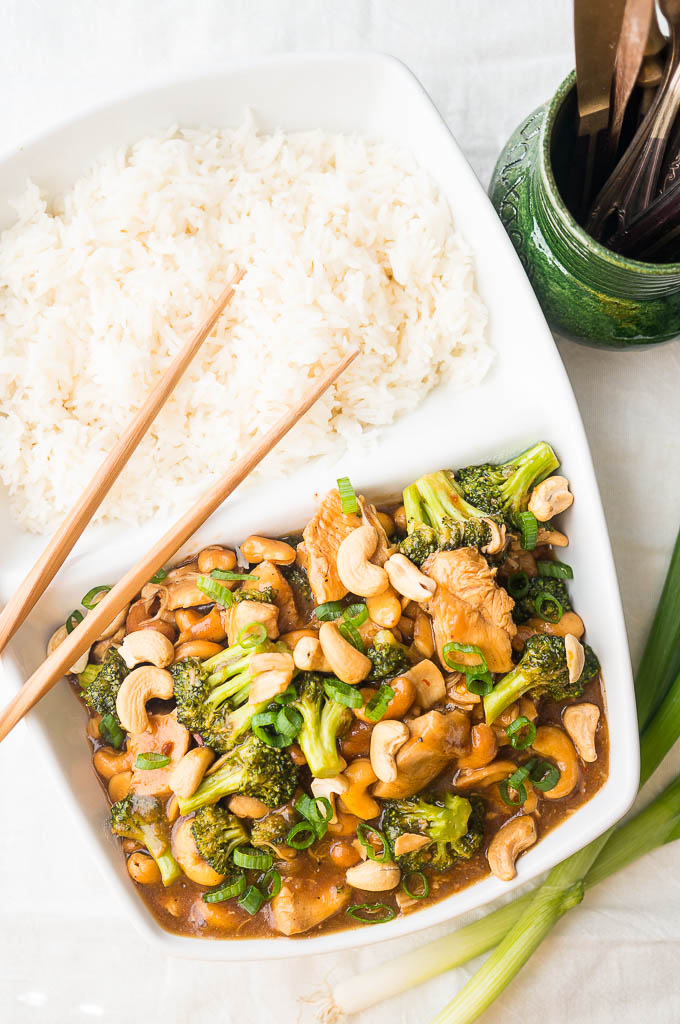 Cashew Chicken with Broccoli topped with green onions, and white rice in a white dish with wooden chopsticks on a white background. A green mug with copper utensils.