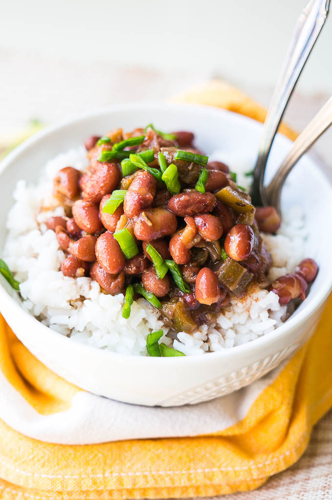 Red beans and white rice in a white bowl on a yellow napkin.