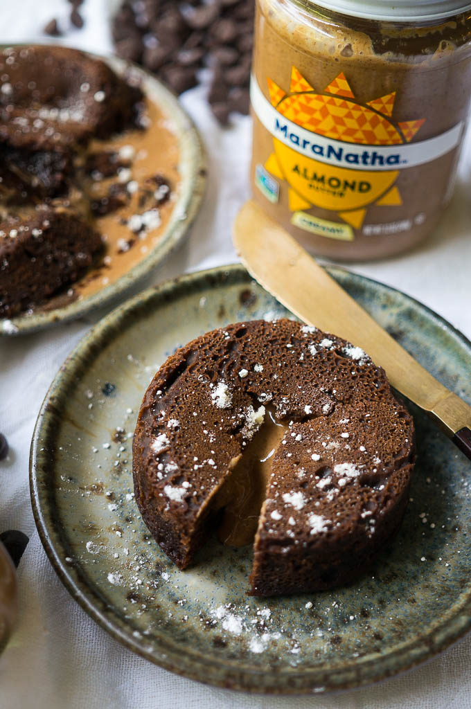 Dark Chocolate Almond Butter Lava Cakes dusted with powdered sugar on a speckled ceramic plate with a copper knife on a white tablecloth. Jar of Maranatha Almond butter and chocolate chips.