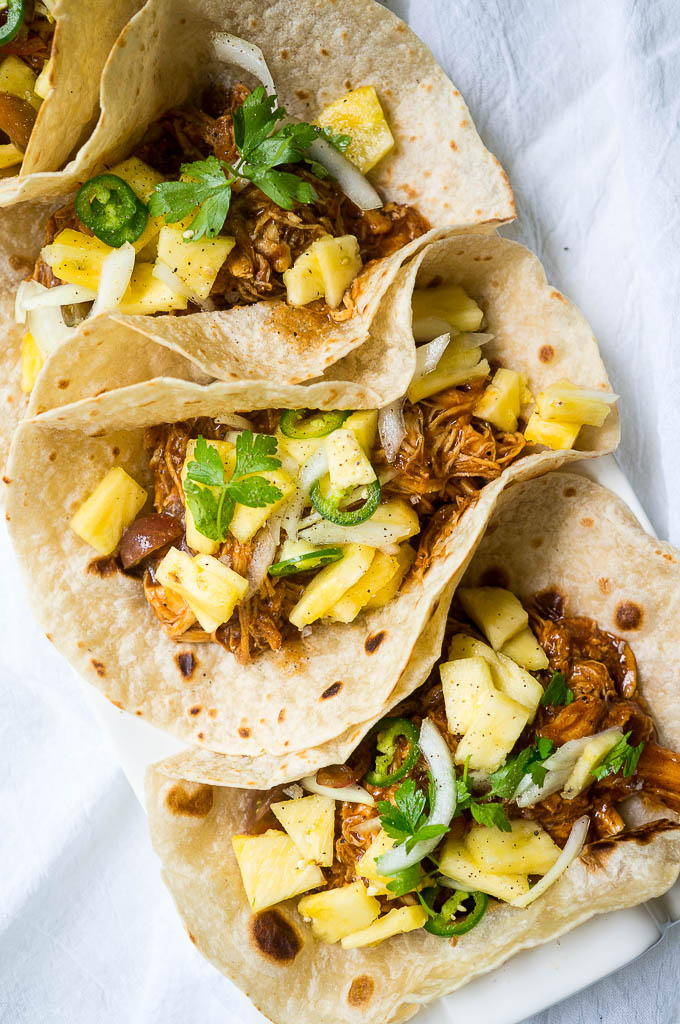 BBQ Chicken Tacos topped with Pineapple Slaw, jalapeño , and cilantro in a white flour tortilla on a white background.