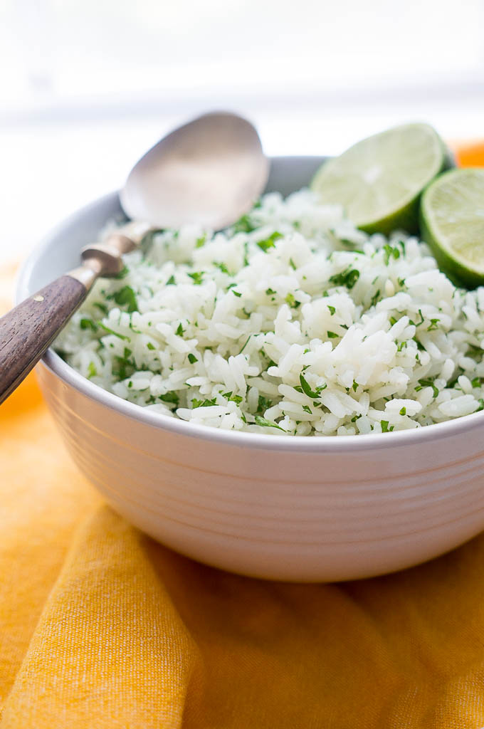 Cilantro Rice topped with lime wedges and a copper and wooden spoon in a white bowl on a yellow napkin.