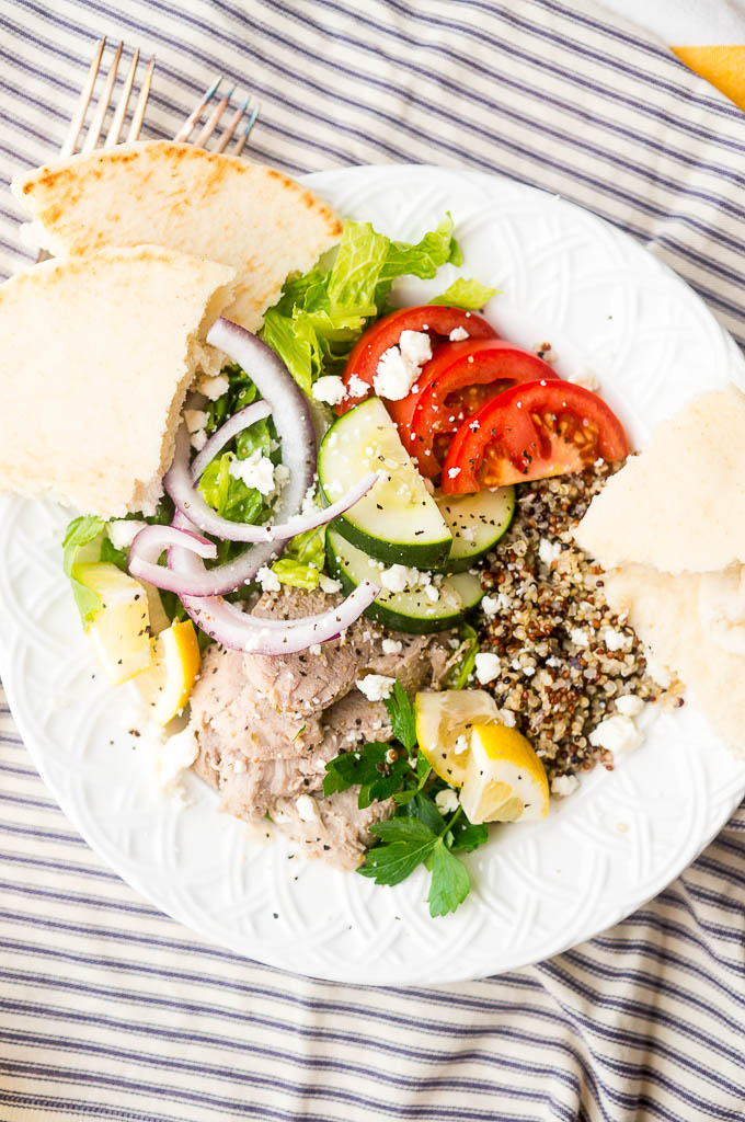 Greek Pork and Quinoa Bowl with red onions, romaine lettuce, sliced tomatoes, cucumber, lemon wedges, and feta cheese on a wide white bowl and a grey and white striped napkin, served with pita bread.