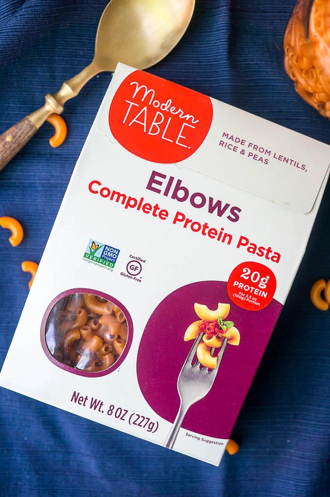 Box of Modern Table Elbow macaroni complete protein pasta on a blue napkin.