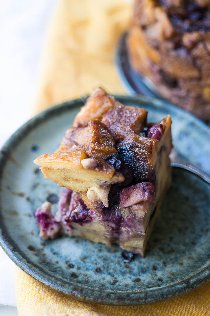 Blueberry Apple Bread Pudding on a speckled blue plate on a yellow tablecloth.