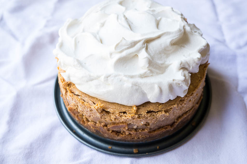 Cheesecake with whipped cream on a white background.