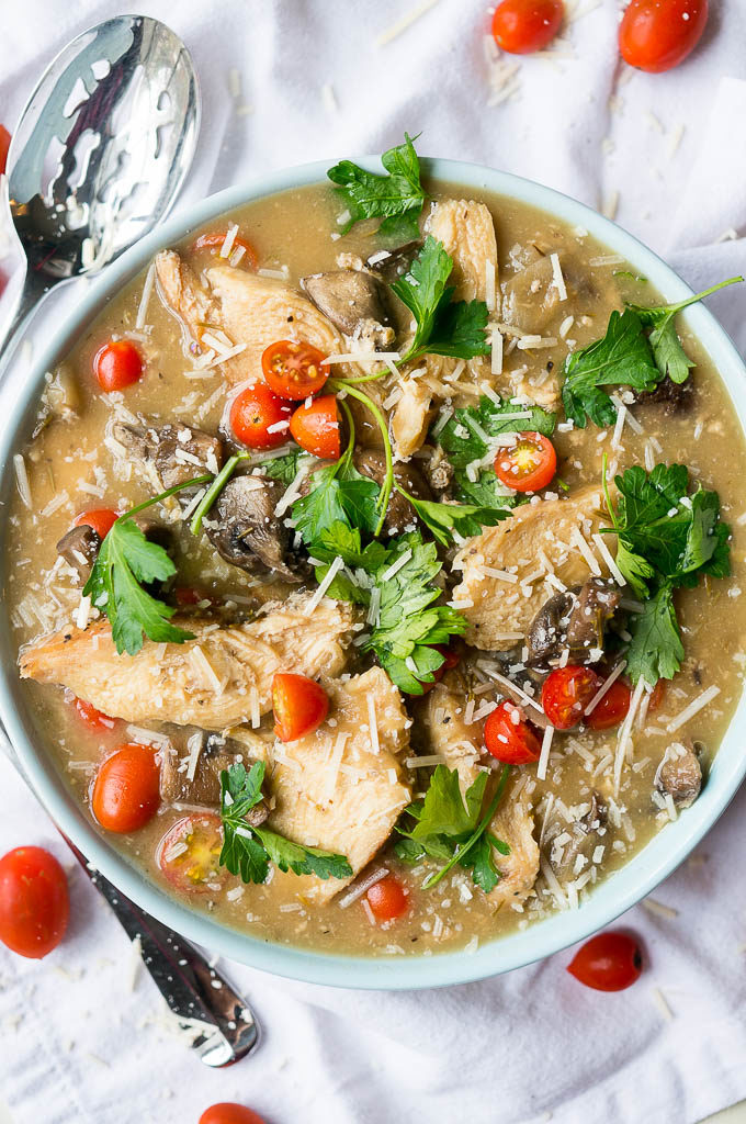 Chicken, cherry tomatoes, and mushrooms in a light blue bowl on a white napkin.