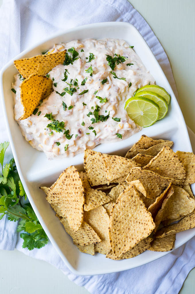 Creamy chicken and cheese dip with tortilla chips in a white dish.
