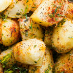 Herb Roasted Potatoes on a glass platter with dipping sauce.