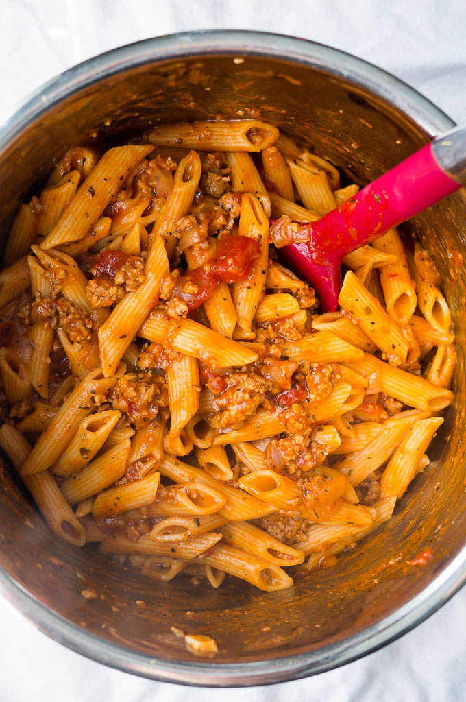 Penne pasta in red sauce with sausage in a metal pot.