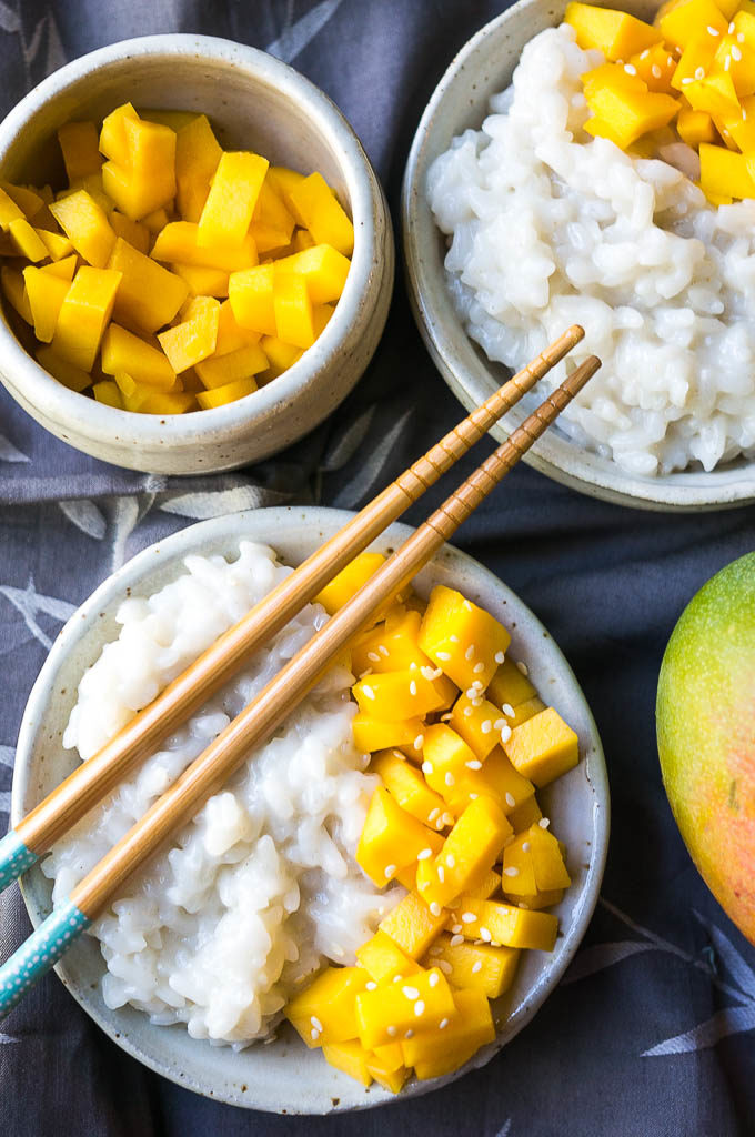 Mango, white rice, and sesame seeds on a white plate on a gray background.