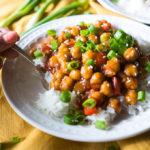 Chickpeas and white rice on a white plate with green onions on a yellow napkin.