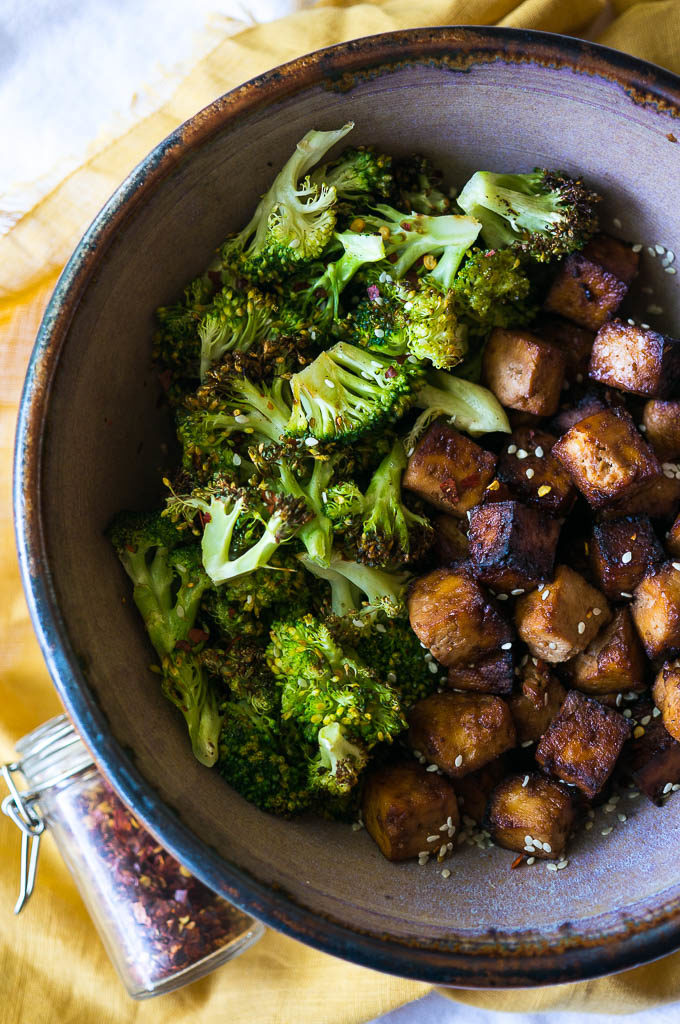 Crispy tofu and roasted broccoli in a pottery bowl