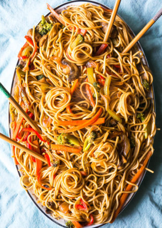 veggie lo mein with carrots on a light blue background